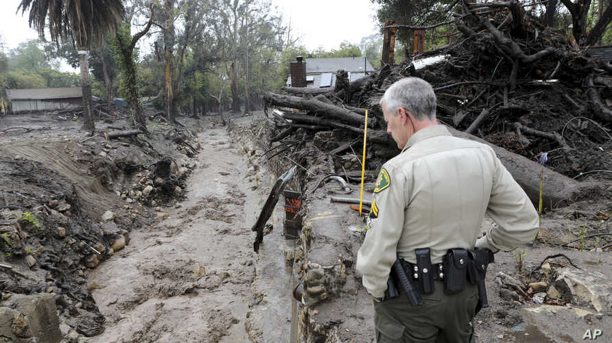 Senior deputy Jeff Farmer with the Santa Barbara County Sheriff office checks the Montecito Creek to make sure it is flowing correctly, March 22, 2018.