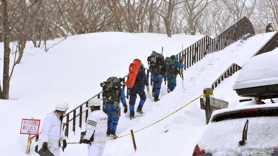 Rescue workers climb toward a mountain for searching missing people after an avalanche near a ski resort in Nasu town, north of Tokyo, Japan, March 27, 2017.