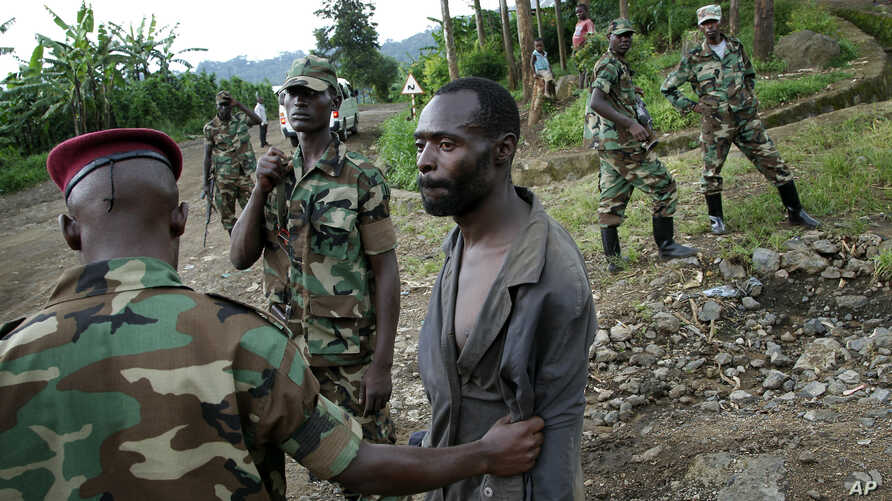 FILE - Congolese  M23 rebel fighters detain a man they suspect to be an FDLR (Force Democratique de Liberation du Rwanda) rebel returning from an incursion into Rwanda Near Kibumba, north of Goma, Nov. 27, 2012.