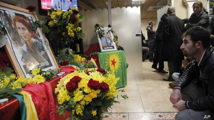 A man reacts next to portrait of Sakine Cansizt inside the Kurdish cultural center in Paris, France, January 10, 2013.
