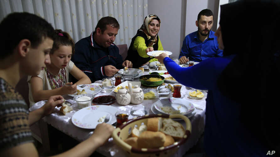 On the first day of the Muslim holy month of Ramadan, Selami Aykut, 38, center, and his family observe the sahoor  traditional breakfast of Ramadan, in Istanbul, after being woken by street drummers early Monday, June 6, 2016.