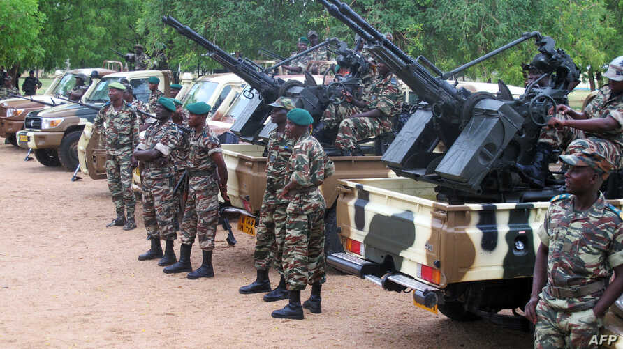 FILE - This photo taken June 17, 2014 shows Cameroonian soldiers standing next to pick up trucks with mounted heavy artillery in Mora, northern Cameroon, which houses a military base where human and logistical resources have been mobilized to face ar...
