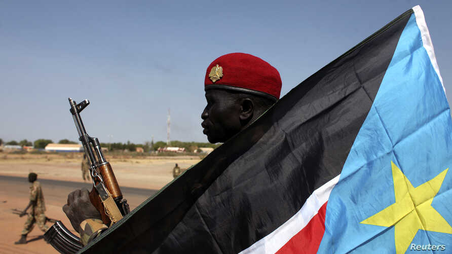 A soldier with the Sudan People's Liberation Army - the army of the Republic of South Sudan - is pictured behind a South Sudan flag as he sits on the back of a pick-up truck in Bentiu, Unity state, Jan. 12, 2014.