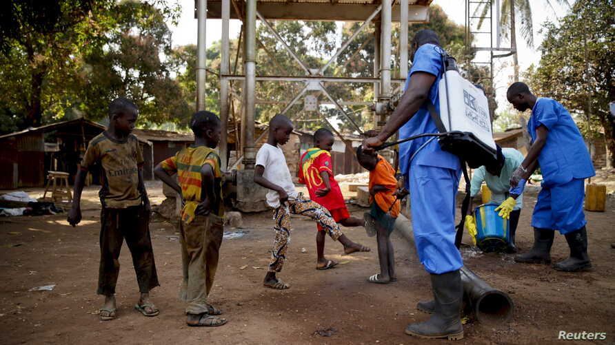Children come forward to get their feet disinfected after a Red Cross worker explained that he was spraying bleach, and wasn't spraying the village with the Ebola virus, in Guinea's Forecariah district, Jan. 30, 2015.