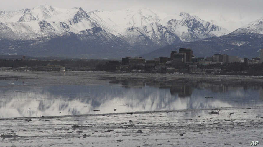 FILE- In this Feb. 12, 2016, photo, the Chugach Mountains and the buildings of downtown Anchorage, Alaska, are reflected in the still waters of Cook Inlet. Oil from an underwater pipeline leak was discovered in the inlet, April 1, 2017.