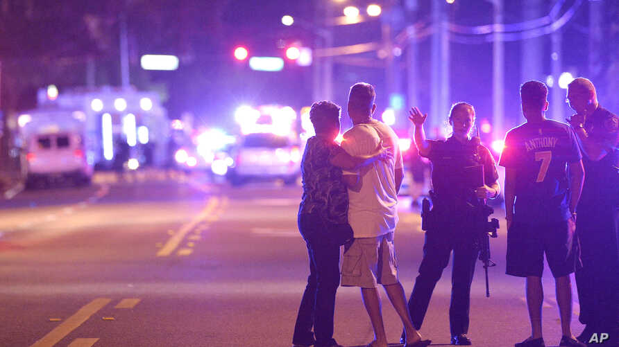 FILE - Orlando Police officers direct family members away from a fatal shooting at Pulse Orlando nightclub in Orlando, Fla.