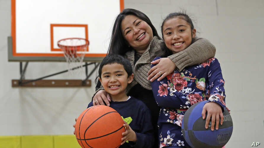 Lara Mae Chollette, a coach of youth soccer and basketball, poses for a photo with her son Jaylen, 7, left, and daughter Linda, 10, at a community gym in Seattle.