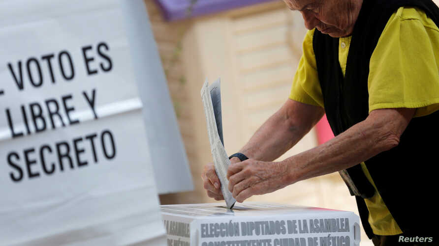 A woman casts her ballot during the election of 60 deputies, to form the Constituent Assembly that will create a constitution for Mexico City, in Mexico City, Mexico, June 5, 2016.