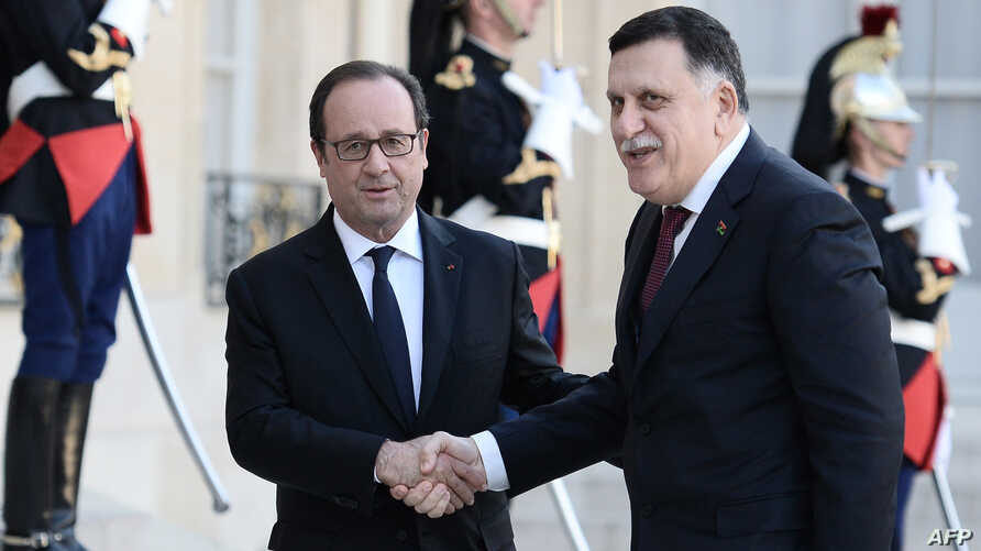 French President Francois Hollande (L) welcomes Prime Minister of Libya's Government of National Accord, Fayez al-Sarraj, upon his arrival at the Elysee Palace in Paris, Sept. 27, 2016.