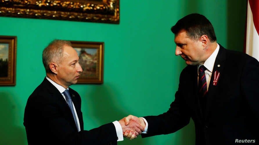 FILE - Latvia's President Raimonds Vejonis (R) shakes hands with his nominated Prime Minister Janis Bordans of New Conservative Party in Riga, Latvia, Nov. 7, 2018. On Wednesday, Bordans abandoned efforts to form a government.