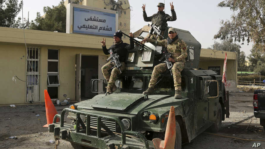 Members of Iraqi security forces flash victory signs outside al-Salam hospital after retaking the facility from Islamic State militants, in Mosul, Iraq, Jan. 10, 2017.
