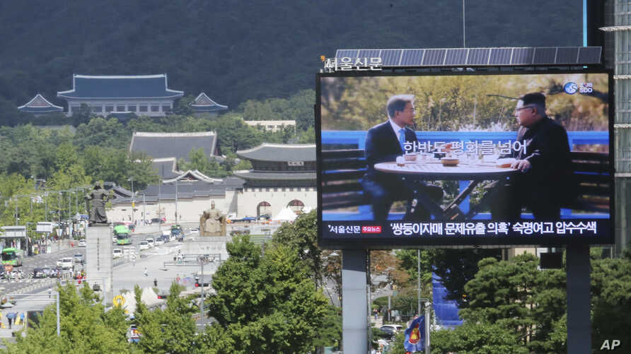 "A TV screen shows a photo of South Korean President Moon Jae-in and North Korean leader Kim Jong UN, right, to advertise upcoming Seoul Defense Dialogue in Seoul, South Korea, Sept. 5, 2018. The sign read: ""Peace on the Korea Peninsula."""