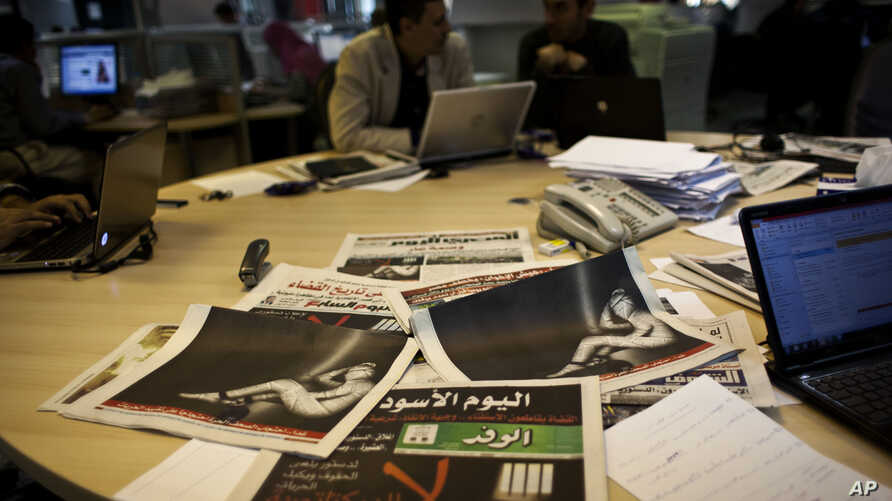 FILE - Egyptian journalists work in the editorial room of the Al-Masry Al-Youm daily newspaper next to copies of Egypt's most prominent newspapers in Cairo, Egypt, Dec. 3, 2012.