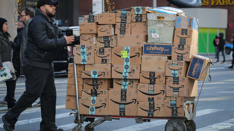 A delivery person pushes a cart full of Amazon boxes in New York City, U.S., Feb. 14, 2019.