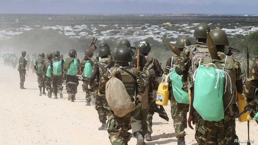 FILE - African Union Mission in Somalia (AMISOM) peacekeepers from Burundi patrol after fighting between insurgents and government soldiers erupted on the outskirts of Mogadishu, May 22, 2012.