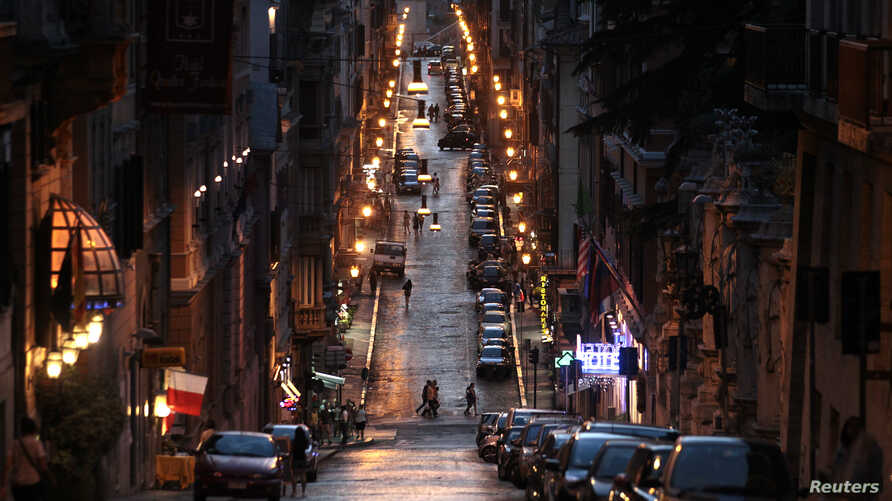A street in downtown Rome glows with the warm light of the old sodium lightbulbs. Rome is in the middle of swapping out the older lights for new, more efficient LED lights.