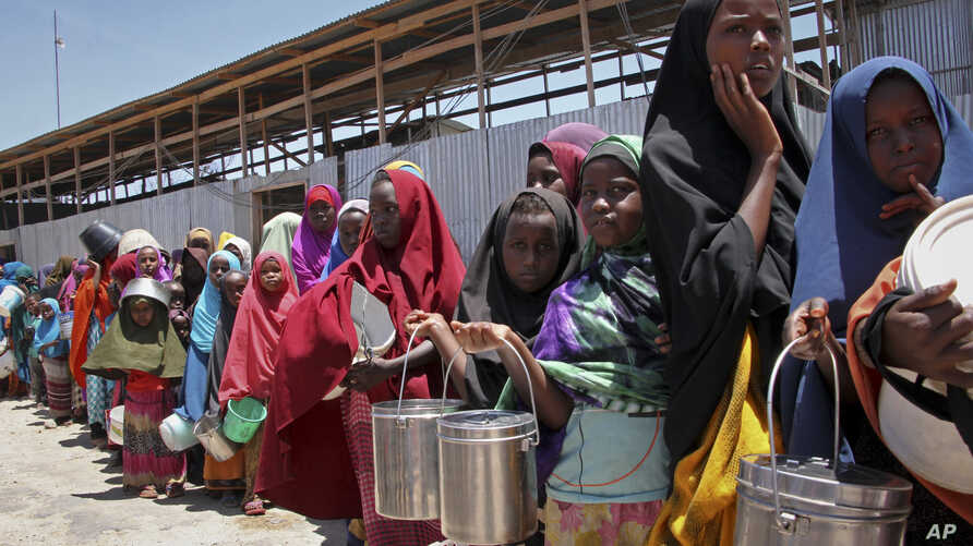 FILE - In this photo taken Feb. 25, 2017, displaced Somali girls who fled the drought in southern Somalia stand in a queue to receive food handouts at a feeding center in a camp in Mogadishu, Somalia.