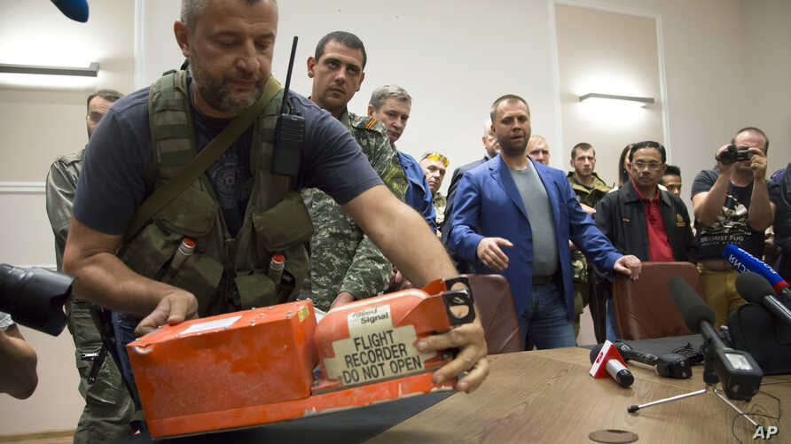 A pro-Russian rebel prepares to turn over recorders from crashed Malaysia Airlines Flight 17 in Donetsk, Ukraine, July 22, 2014.
