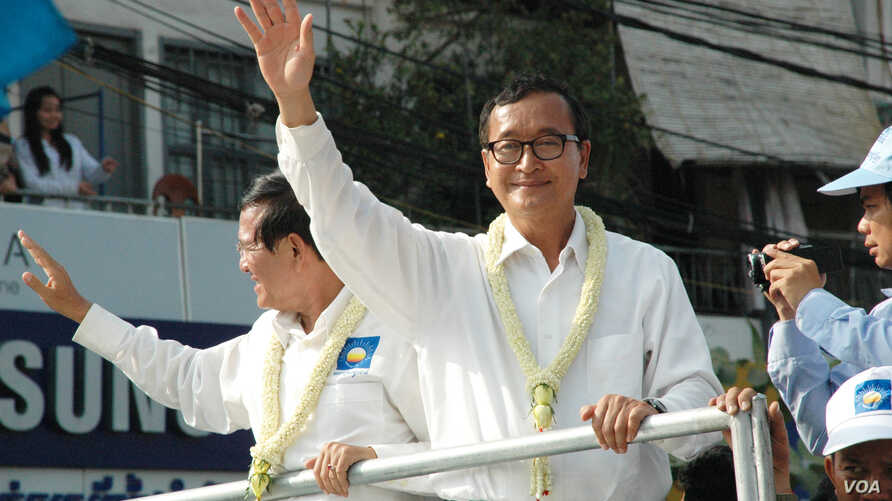 Opposition leader Sam Rainsy (white shirt, right), and deputy opposition leader Kem Sokha (left) wave to people watching the march, Phnom Penh, Cambodia, Dec. 29, 2013. (Robert Carmichael/VOA).