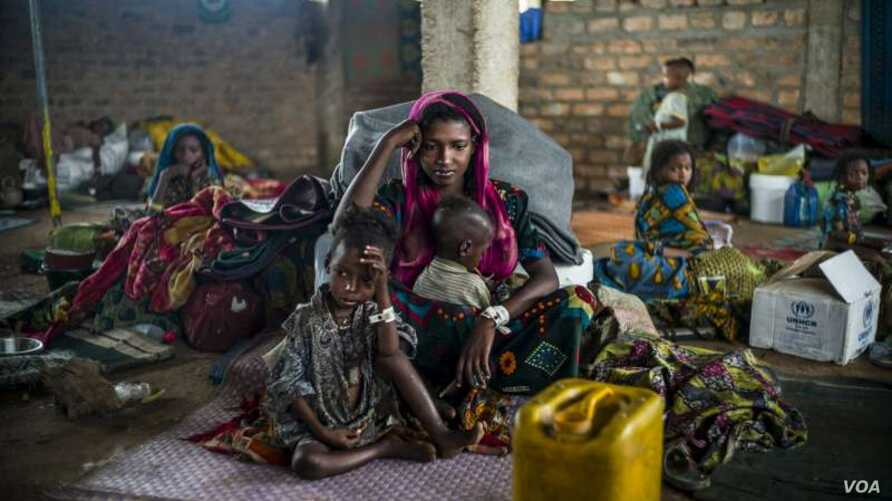 A 19-year-old woman and her children wait for their first hot meal in over two months at the Dosseye refugee camp in Chad.  They arrived the previous day after fleeing violence in C.A.R.