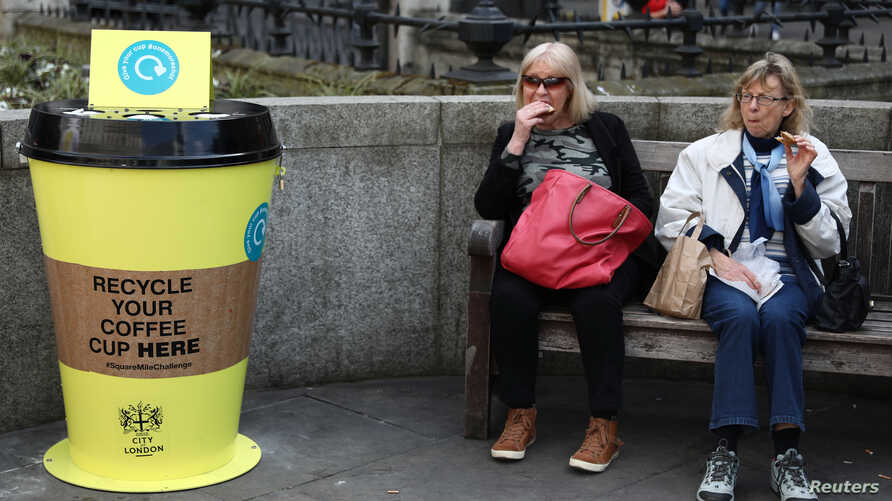 """People sit next to a new coffee cup recycling point in London, April 3, 2017. British lawmakers are considering a """"latte levy"""" to encourage reusable cups and recycling."""