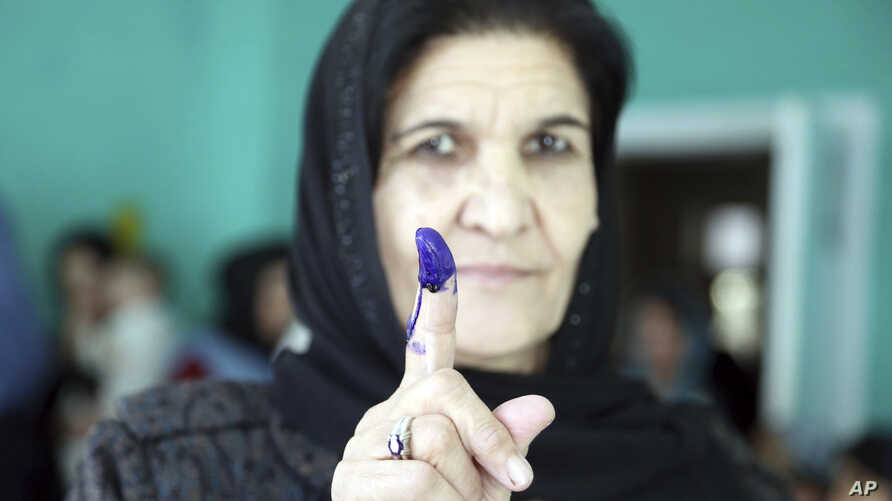 An Afghan woman shows her inked finger after casting her vote at a polling station during the Parliamentary elections in Kabul, Afghanistan, Oct. 20, 2018.