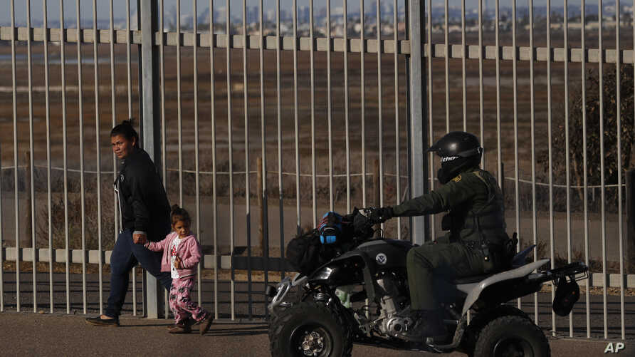 FILE – A migrant and her daughter walk along a secondary b
