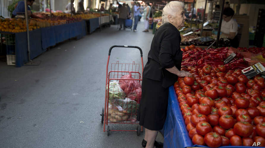 "A elderly woman buys goods at a vegetable market in Athens, on Friday, July 3, 2015. The brief but intense campaign in Greece's critical bailout referendum ends Friday, with simultaneous rallies in Athens for ""Yes"" and ""No"" supporters in what an opin"