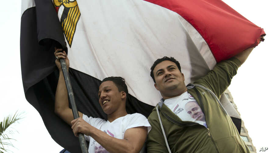 Supporters of President Abdel-Fattah el-Sissi wave a national flag as they celebrate in Mustafa Mahmoud Square after the election commission announced the presidential election results, in Cairo, April 2, 2018. The commission said el-Sissi has won a