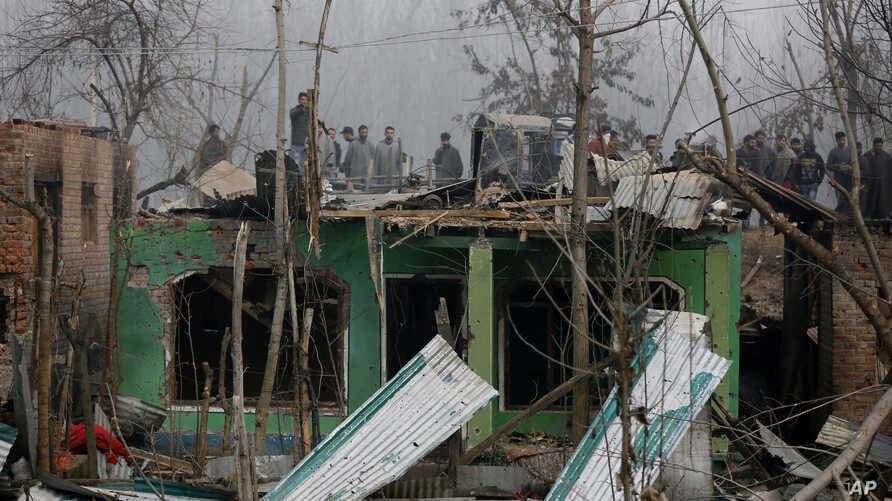 Kashmiri villagers watch the damage to residential houses at the site of a gun-battle in Mujagund area some 25 Kilometers (16 miles) from Srinagar, Indian controlled Kashmir, Dec. 9, 2018.