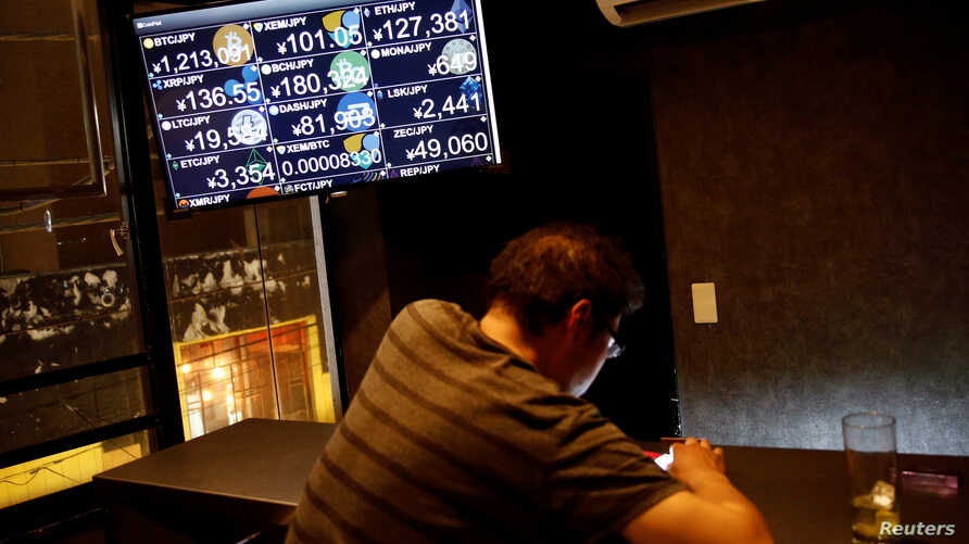 """A monitor shows various cryptocurrencies' exchange rates against Japanese Yen including NEM coin (middle in the top) at a """"nem bar,"""" where customers can pay with NEM coins, in Tokyo, Japan Jan.  29, 2018."""