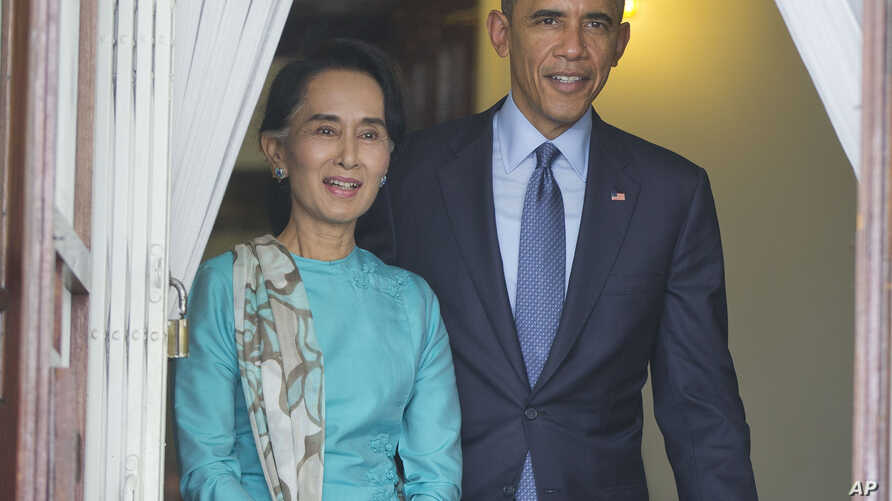 FILE - President Barack Obama, right, walks out with Myanmar's Aung San Suu Kyi at her home before the start of their joint news conference in Yangon, Myanmar.