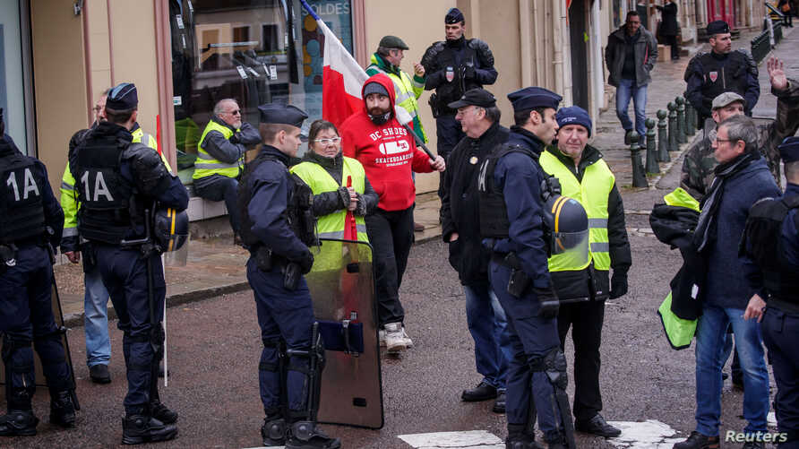 Protesters of the 'Gilets Jaunes' (Yellow Vests) movement await French President Emmanuel Macron's arrival, during his meeting with the mayors of the Saone-et-Loire department, in Autun, France Feb. 7, 2019.