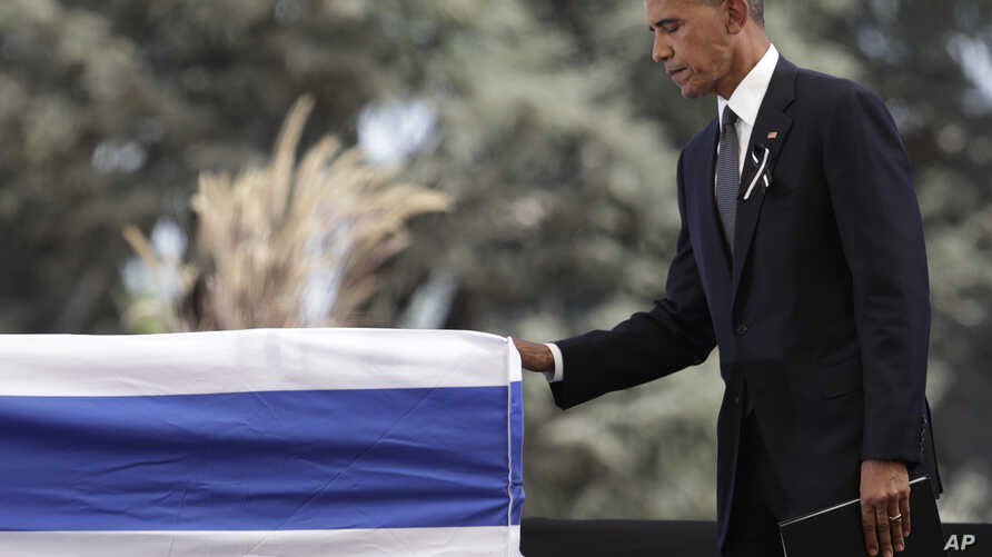 U.S. President Barack Obama touches the casket of former Israeli President Shimon Peres after speaking during the funeral service at Mount Herzl national cemetery in Jerusalem, Sept. 30, 2016.