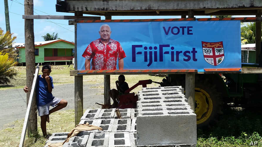 A FijiFirst poster with the image of Fiji Prime Minister Frank Bainimarama hangs at the entrance to a village in Nausori, Fiji, Nov. 7, 2018. Opinion polls indicate Bainimarama is poised to win a second term in Fiji's general election Wednesday after