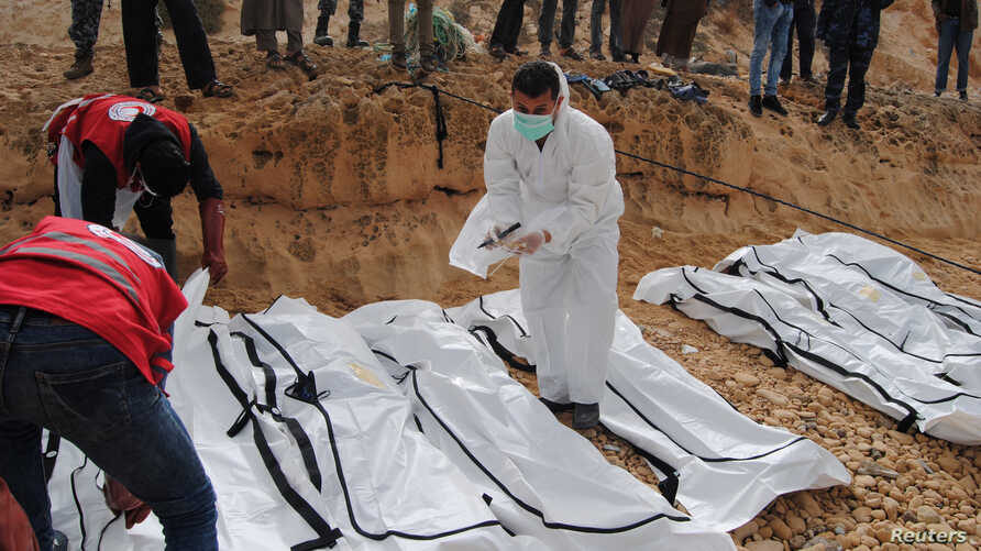 A rescue worker labels bags containing dead bodies of migrants who were washed up on a beach near the city of Zawiya, Libya Feb. 20, 2017.