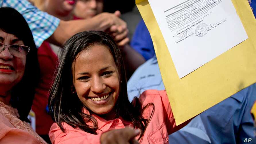 Newly-elected opposition congresswoman Marialbert Barrios holds up her credentials after receiving them from the National Electoral Council (CNE) in Caracas, Venezuela, Dec. 9, 2015.