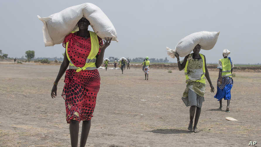 A women walk back to their homes after receiving food distributed by ICRC at a site in Leer County region of South Sudan, Tuesday, April 11, 2017. Two months after a famine was declared in two counties amid its civil war, hunger has become more wides