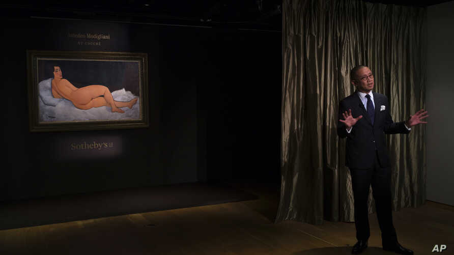 """Kevin Ching, CEO of Sotheby's Asia. speaks next to a painting """"Nu couche"""" by Italian artist Amedeo Modigliani during Sotheby's auction press preview in Hong Kong, April 24, 2018."""