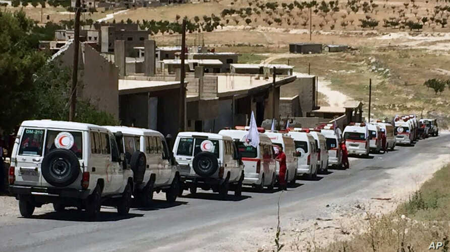 Photo released by the government-controlled Syrian Central Military Media shows ambulances of the Syrian Arab Red Crescent gathering in the Syrian border village of Fleeta, ahead of the evacuations of some Syrian refugees from Lebanon, July 31, 2017.