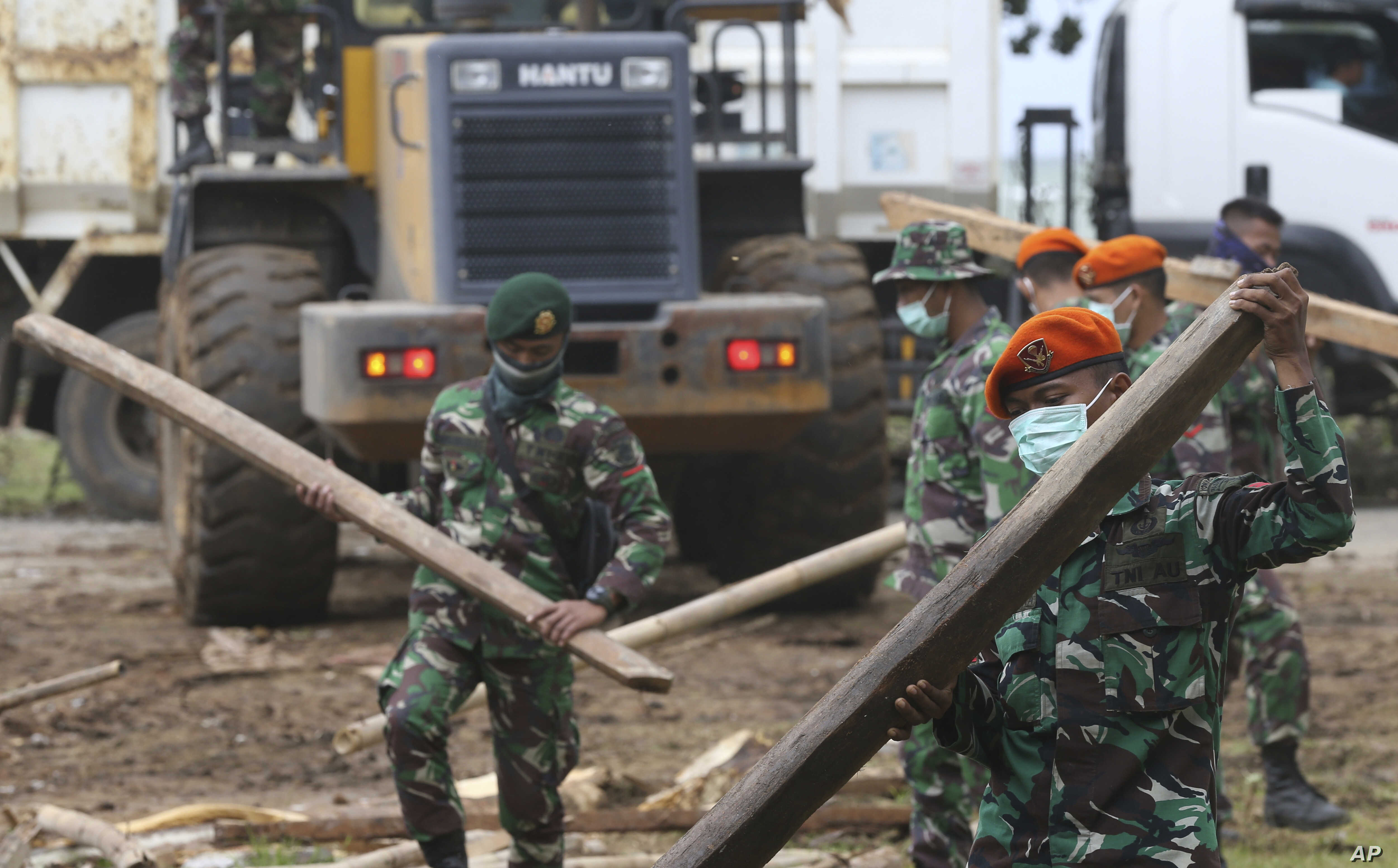 Soldiers remove debris from a damaged house in the tsunami-hit village of Carita, Indonesia, Dec. 28, 2018.