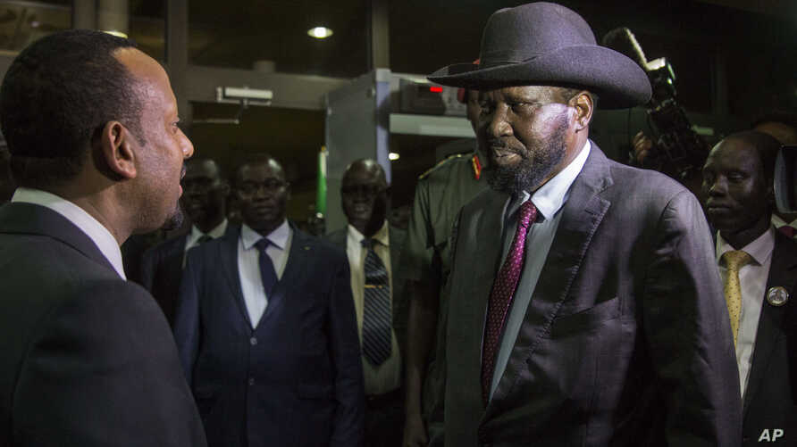 South Sudan's President Salva Kiir, right, is greeted by Ethiopia's Prime Minister Abiy Ahmed, left, as Kiir arrives for a meeting with South Sudan's opposition leader Riek Machar, in Addis Ababa, Ethiopia,  June 20, 2018.