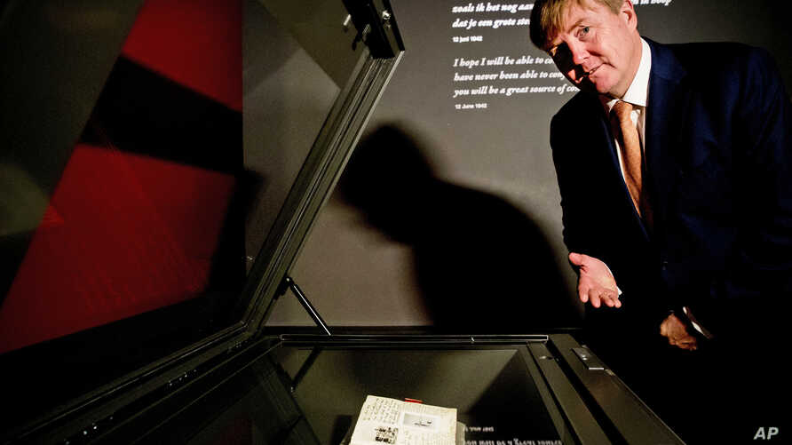 Dutch King Willem-Alexander looks at Anne Frank's diary displayed in the new Diary Room at the renovated Anne Frank House Museum in Amsterdam, Netherlands, Nov. 22, 2018.