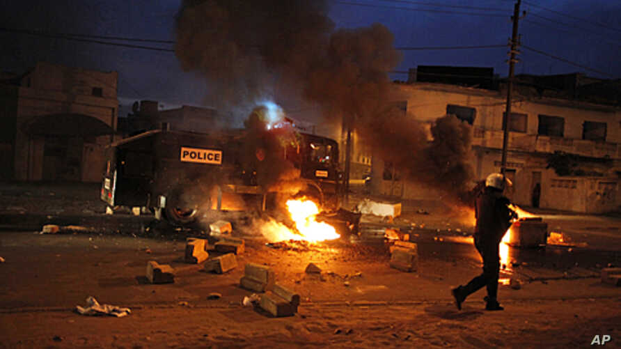 Riot police walk past street fires lit by protesters in Dakar, Senegal, January 31, 2012.