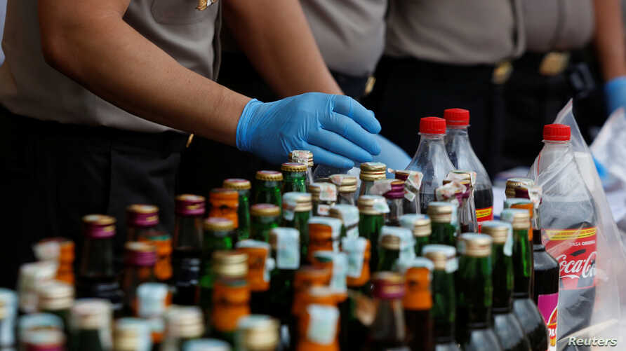 Police prepare evidence during a press conference, April 11, 2018, regarding the arrests of suspects linked to the production and sale of illegal bootleg alcohol, which claimed the lives of more than 80 people this week in Jakarta and nearby West Ja