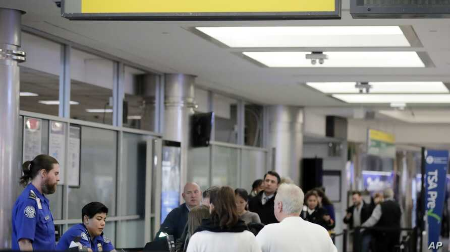 Passengers stand in line as they wait to pass through a Transportation Security Administration checkpoint at LaGuardia airpor, Jan. 7, 2019, in New York.