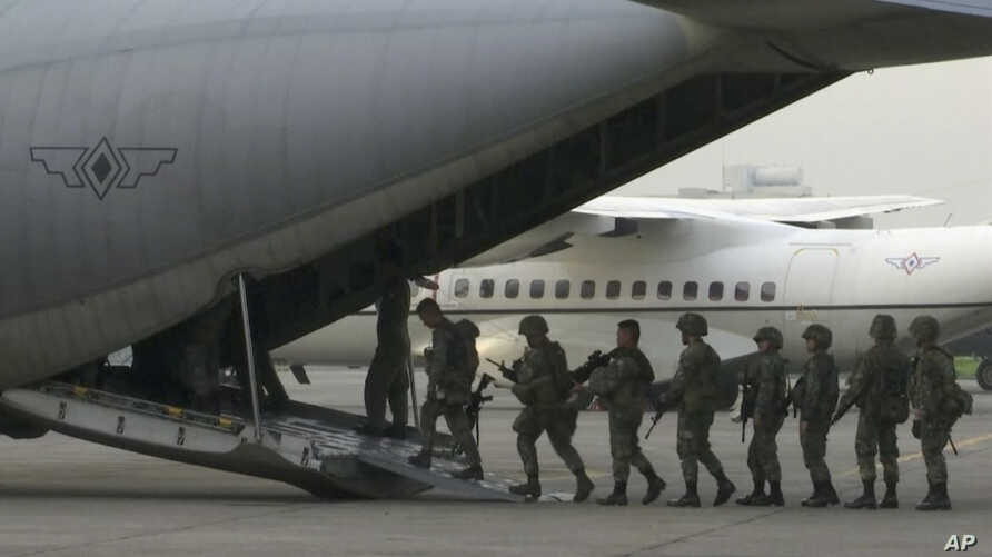 In this image made from video, marines board a transport plane in Manila, Philippines, June 1, 2017. A marine battalion left an air force base in Manila on deployment to the southern city of Marawi where ongoing violence has killed scores of people.