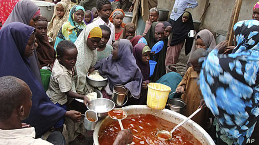 Women and children from southern Somalia receive cooked food at a distribution center in Mogadishu, Somalia, August 25, 2011