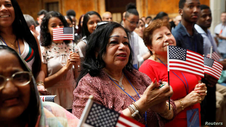 New citizens stand during a U.S. Citizenship and Immigration Services (USCIS) naturalization ceremony at the New York Public Library in Manhattan, New York, July 3, 2018.