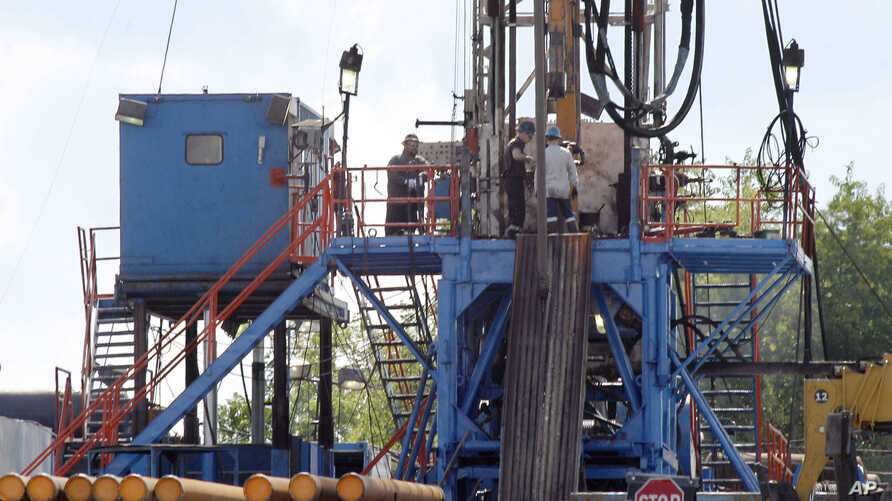 FILE - A crew works on a gas-drilling rig at a well site for shale-based natural gas in Zelienople, Pa., June 25, 2012.